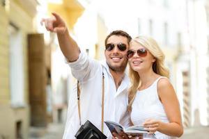Pareja con cámara y guía de viajeros en la ciudad
