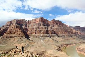 homme avec bras levé sur grand canyon