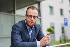 Young businessman with beard eating in front of office block.