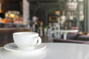 Taza de café en la cafetería desenfoque de fondo foto