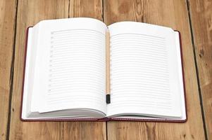 rood lederen notitieboek met potlood op hout achtergrond