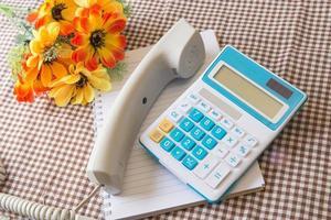 Nota de papel, teléfono, calculadora y concepto de flor de oficina w foto