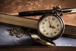 Pocket watch with antique book and pen.