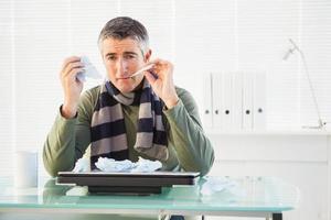 hombre enfermo tomando su temperatura foto