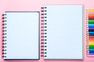 Notebook and colored pencils on pink background