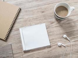 disco compacto en blanco, auriculares, notebook y café sobre fondo de madera foto