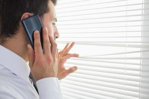 apuesto hombre de negocios espiando a través de la persiana mientras llamando foto