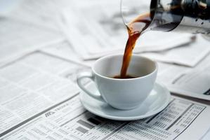 Coffee being poured into a cup on top of a newspaper