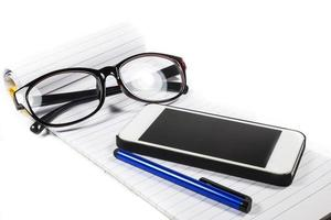 glasses notebook pen telephone