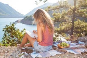 Chica adolescente rubia sentada en una cubierta, picnic, montañas