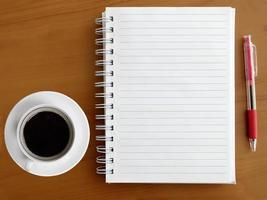 Notebook, pen and cup of coffee on wooden table photo
