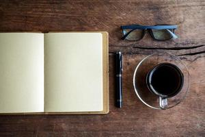 Cup of coffee with notebook on old wood photo