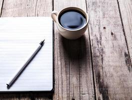 cuaderno con bolígrafo y café en la mesa de madera vieja