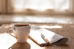 Cup of black coffee, newspaper and a pen photo