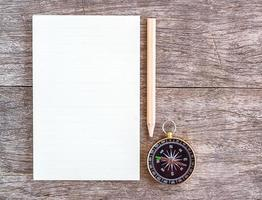Open blank notebook with pencil and compass on wooden background photo