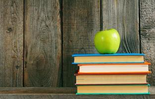 Multi-coloured books and green apple .