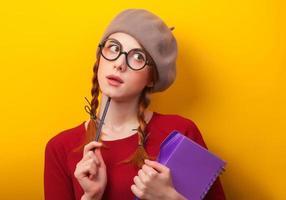 ragazza rossa con taccuino e matita su sfondo giallo.