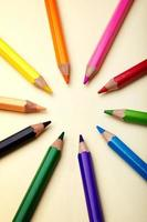 Color pencils in arranged in color wheel colors on paper background