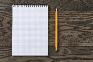 cuaderno abierto para escribir o dibujar en la mesa de roble foto