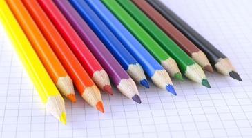 Lápices de colores en el papel marcado del bloc de notas