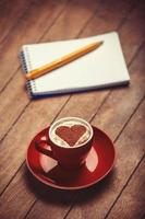 Cup of coffee with notebook on a wooden table.