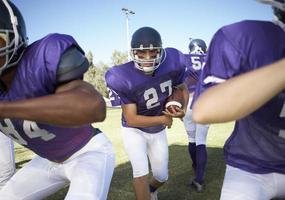 Jugadores jugando fútbol americano en el campo foto