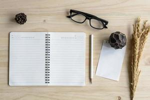 cuaderno en blanco con gafas en el escritorio de madera foto