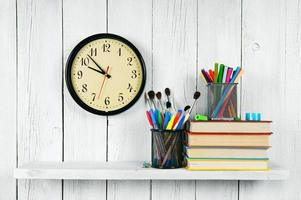 Watches, books and school tools on wooden shelf.