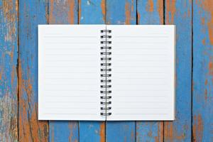 Page of notebook on wooden background photo