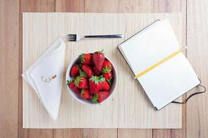 Bowl of fresh strawberries with a notebook