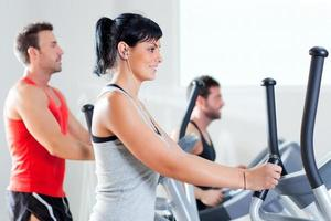 Men and woman working out on elliptical cross trainer at gym