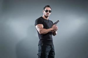 Action hero muscled man holding a gun. Wearing black t-shirt.