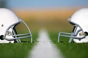 Two American football helmets on the field facing each other