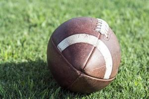 Close up of American football sitting on grass