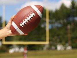 American Football in Hand over Field with Goal Post photo