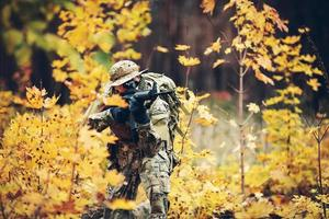 soldier with rifle in the forest photo