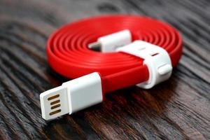 Red USB cable on wooden table photo