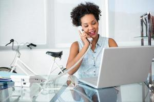 Young woman using telephone and laptop