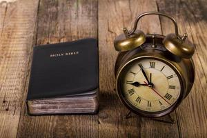 Bible with clock on wood photo