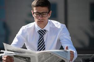 Businessman reading newspaper during break