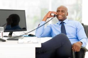 empresario afroamericano con teléfono fijo