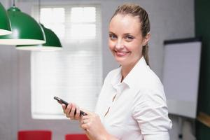 Blonde smiling businesswoman using smartphone