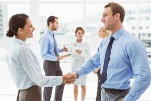Executives shaking hands with colleagues behind