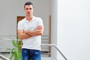 Man in a polo shirt stands leaning on railing photo