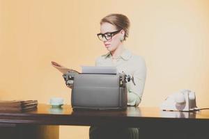 Vintage 1950 joven secretaria sentada detrás del escritorio leyendo newspap foto
