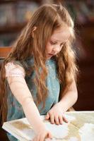 Young girl looking through an atlas photo