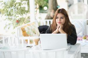 Asia young business woman sitting in cafe with laptop