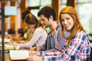 Student looking at camera while studying with classmates