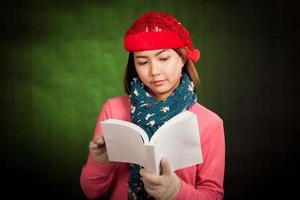 Asian girl with red christmas hat read a book