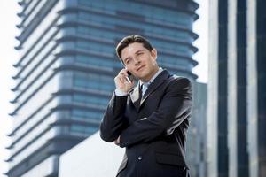 empresario atractivo en traje y corbata hablando por teléfono móvil